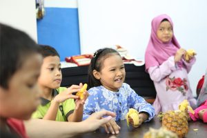 Children in Malaysian orphanage eating fruit